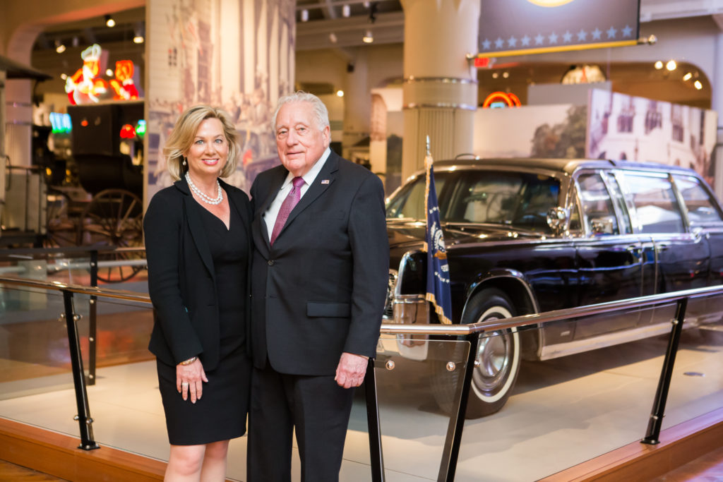 Authors Lisa McCubbin and Secret Service Agent Clint Hill in front of presidential vehicle SS-100-X at the Henry Ford Museum in Dearborn, MI. KMS Photography.